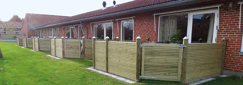 Ein niedriger Gartenzaun bietet den Bewohnern eines Pflegeheims etwas Privatsphäre auf ihren kleinen Terrassen. Ein Tor im gleichen Design wie der Zaun bietet Zugang zu einem gemeinsamen Rasen | Poda Zaun