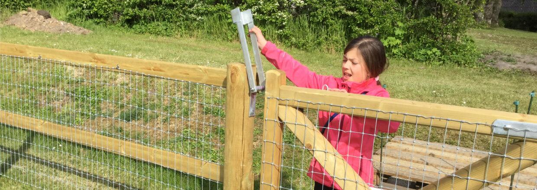 Ein Mädchen ist dabei, den Verschluss eines Holztores zu öffnen | Poda Zaun