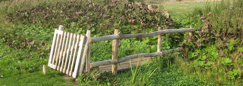 Ein Klapptor ermöglicht den Zugang zu einem Gehege über eine Holzbrücke. Die Holzbrücke führt über einen Graben und hat ein Geländer aus Holzpfälen | Poda Zaun