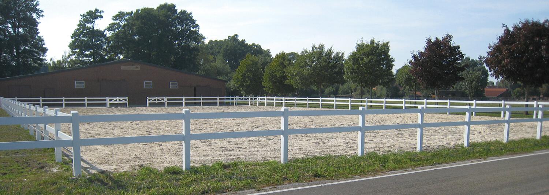 Der Reitplatz neben dem Stall ist von einem weißen Pferdezaun umgeben | Poda Zaun