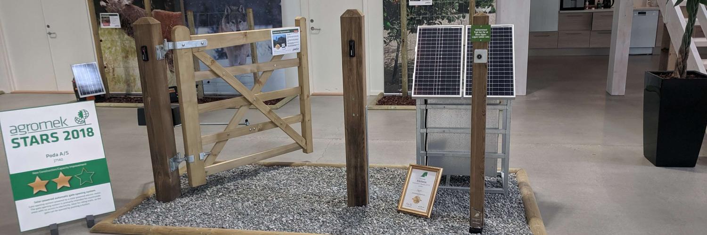 Solarbetriebene Torautomatik, montiert an einem kleinen Holztor im Poda Ausstellungsbereich | Poda Zaun