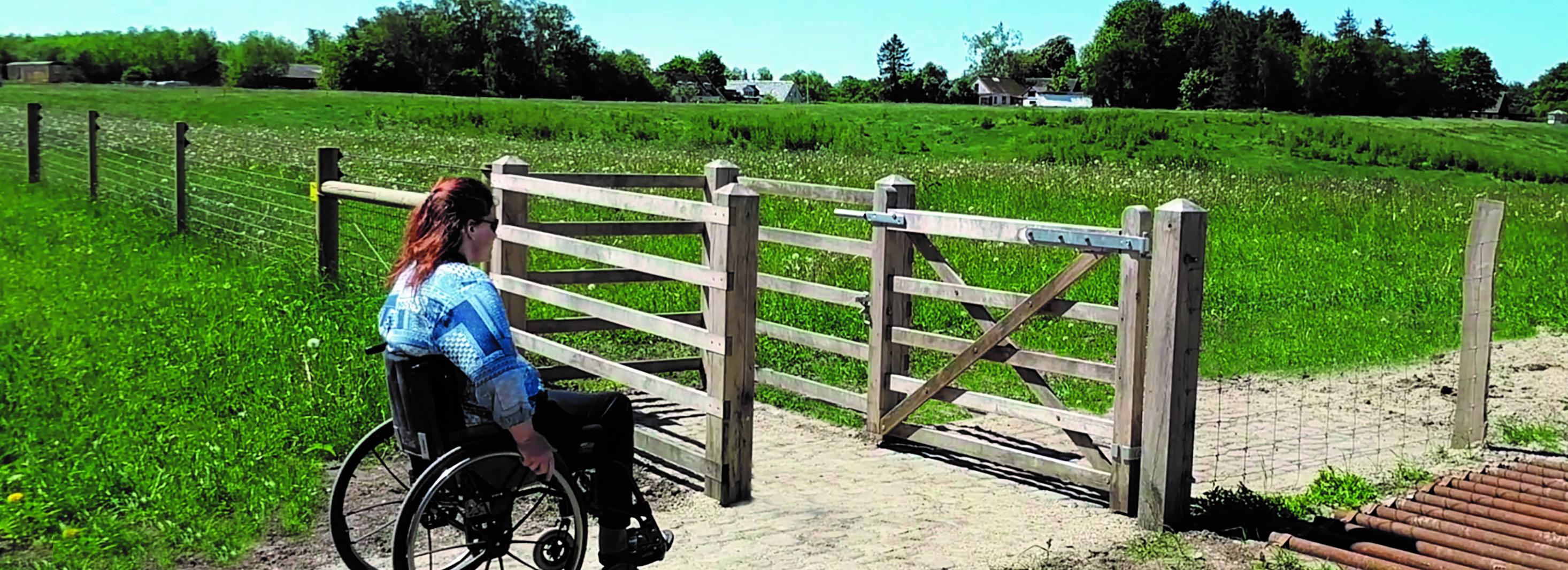 Eine Frau im Rollstuhl ist auf dem Weg zu einem HandyGate. Die Zugangsschleuse bietet Zugang zu einem eingezäunten Bereich mit Tieren | Poda Zaun