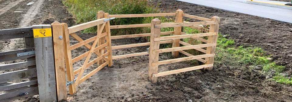 Neben einem Tor in einem eingezäunten Naturbereich wurde eine HandyGate Zugangsschleuse angebracht | Poda Zaun