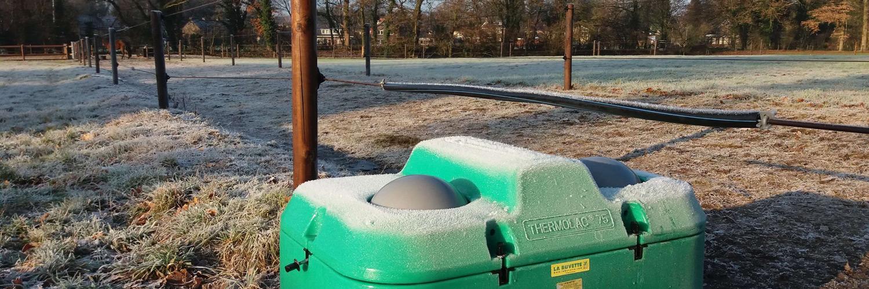Et helårsdrikkekar er placeret under et el-hegn og heste på begge sider af hegnet kan derfor drikke vand fra karret   Poda Hegn