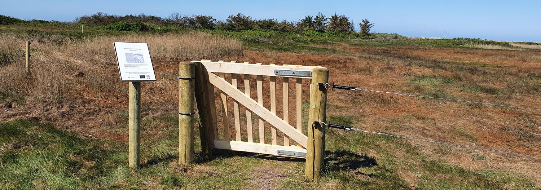 En klaplåge giver folk til fods adgang til en indhegning i et naturområde med lyng | Poda Hegn