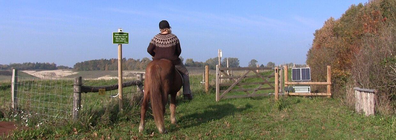 Kvindelig rytter til hest afventer at trælågen foran hendes hest åbnes af en soldrevet lågeautomatik | Poda Hegn