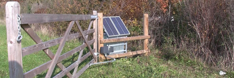 En stor trælåge glider stille op ved hjælp af en soldrevet lågeautomatik | Poda Hegn