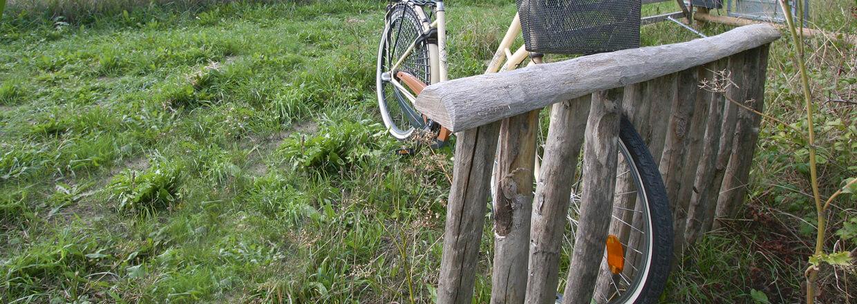 En damecykel holder parkeret i et cykelstativ lavet af træpæle | Poda Hegn