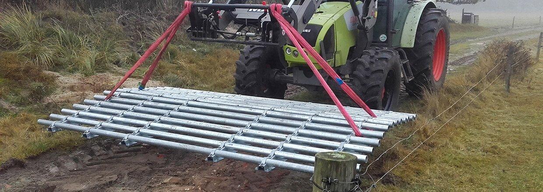 En traktor flytter en færist til en ny placering. Denne flytbare færist kan kun benyttes af terrængående køretøjer | Poda Hegn