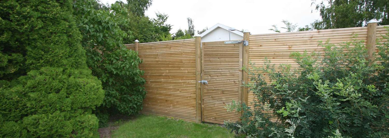 Et havehegn afgrænser en have. En dør i raftehegnet giver adgang til den anden side | Poda Hegn