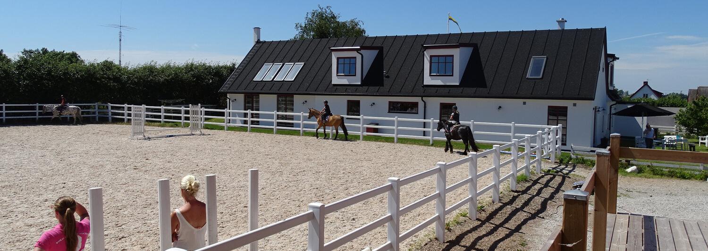Tre rideskoleelever til hest, fører deres heste rundt langs en ridebanes hvide lægtehegn | Poda Hegn