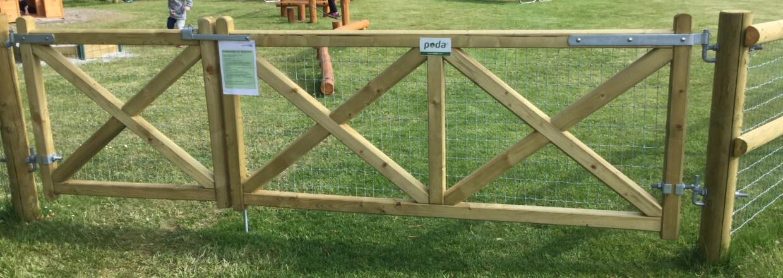 En Country Estate dobbeltlåge tillader nem adgang til en indhegnet legeplads. Dobbeltlågen består af henholdsvis en lille og en stor trælåge | Poda Hegn