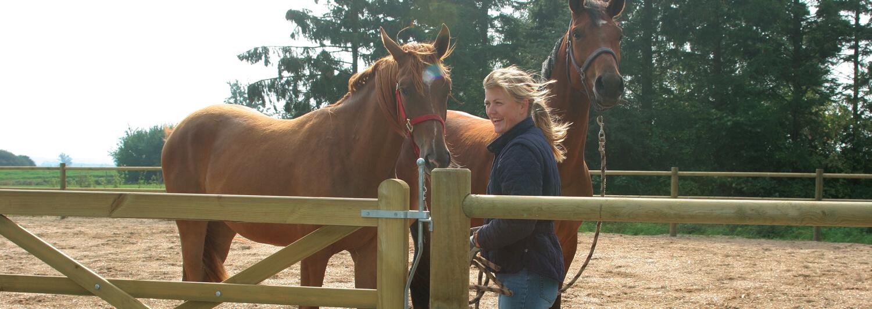 En kvinde står sammen med to brune heste ved trælågen, der giver adgang til en ridebane | Poda Hegn
