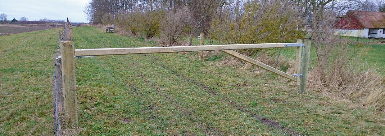 En vejbom i træ afspærrer en markvej | Poda Hegn