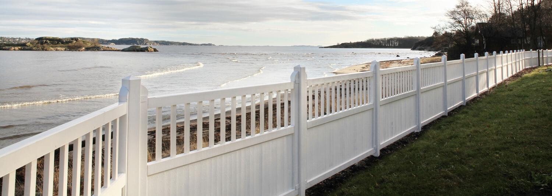 Et hvitt stakitt i tre står i skillet mellom en hage og en strand | Poda Gjerder