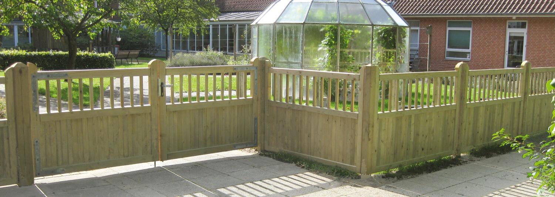 Ett robust Country Garden-staket och en träport avgränsar en uteplats på ett vårdhem | Poda Stängsel