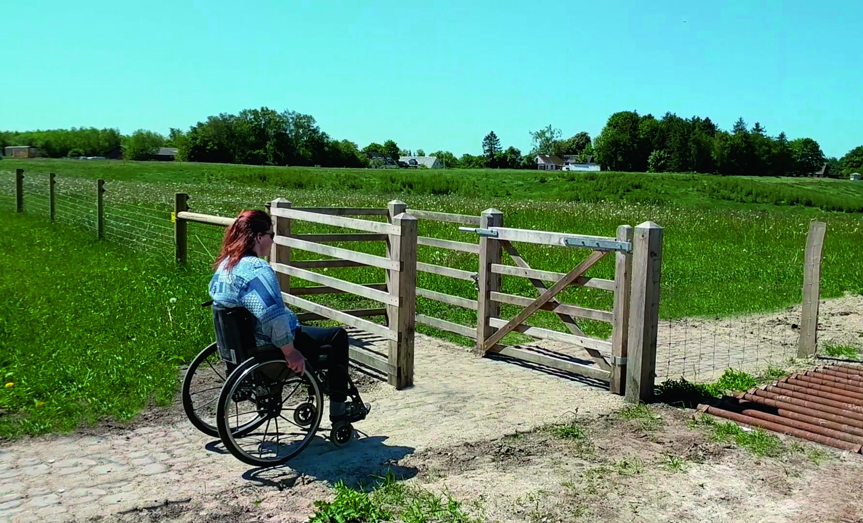En kvinna i rullstol är på väg mot en HandyGate. Rullstolsslussen ger åtkomst till ett inhägnat område med djur | Poda Stängsel
