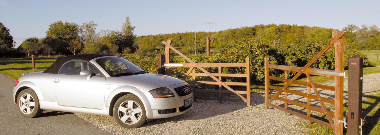 En bil står still i slutet av en infart i väntan på att den dubbla grinden av lövträ ska öppnas | Poda Stängsel