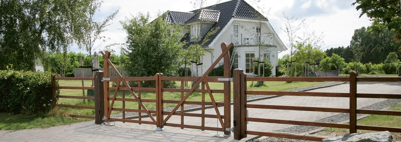 Ett set grindar i lövträ spärrar av infarten till en snygg villa med vita väggar och ett svart tegeltak | Poda Stängsel