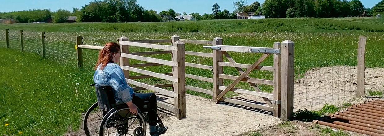 En kvinde i kørestol er på vej hen til en HandyGate. Kørestolsslusen giver adgang til et indhegnet område med dyr | Poda Hegn